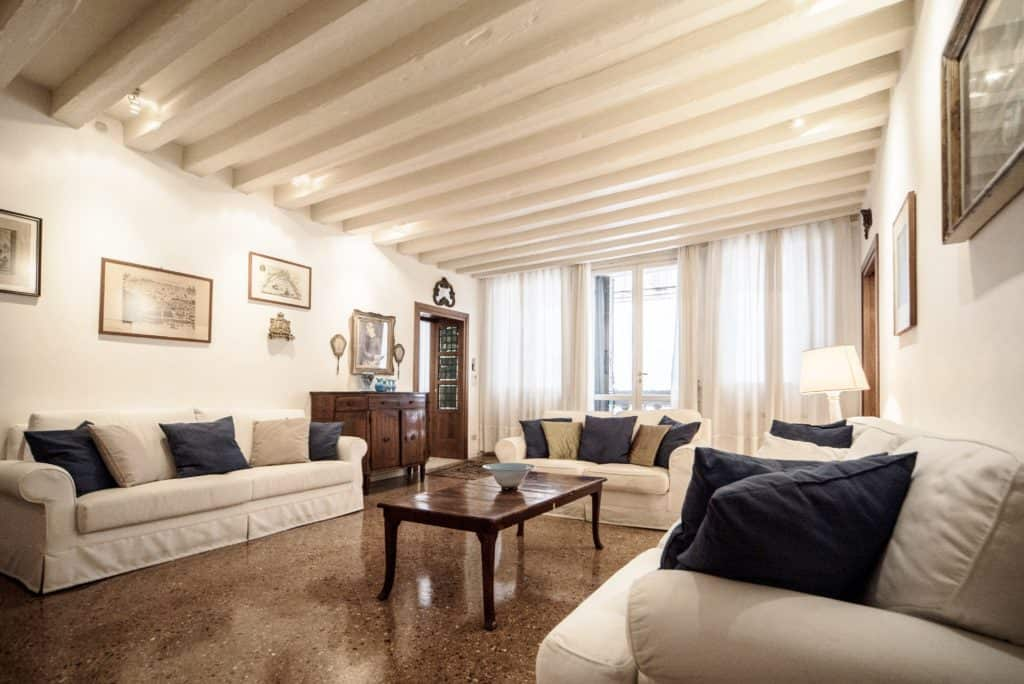 Leftt side of luminous living room with ancient Venetian furnishing and white sofas - Accademia Terrazza Apartment