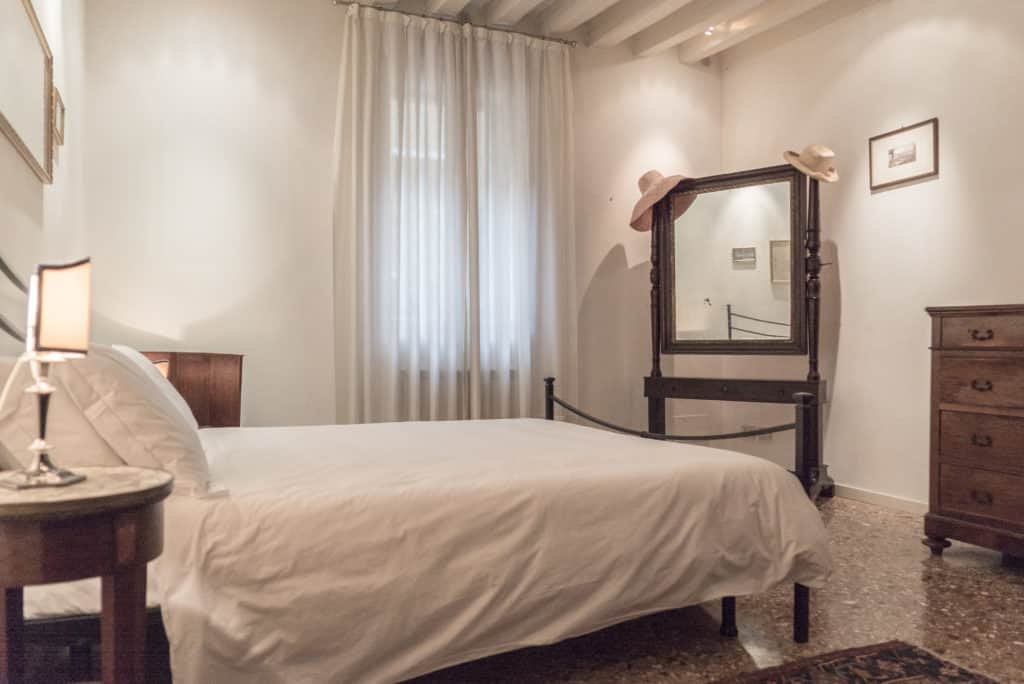 Bedroom with double bed and ancient Venetian mirror - Accademia Terrazza Apartment