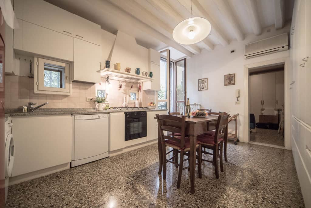 Right side of spacious kitchen with dining table and terrace door - Accademia Terrazza Apartment