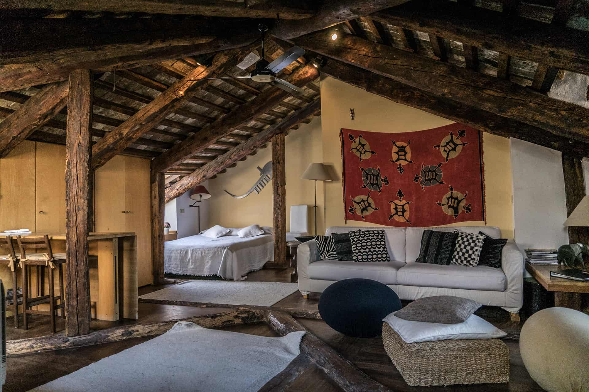 Comfortable double bed and living room in a single large open space with wooden beams - Altana Studio Apartment