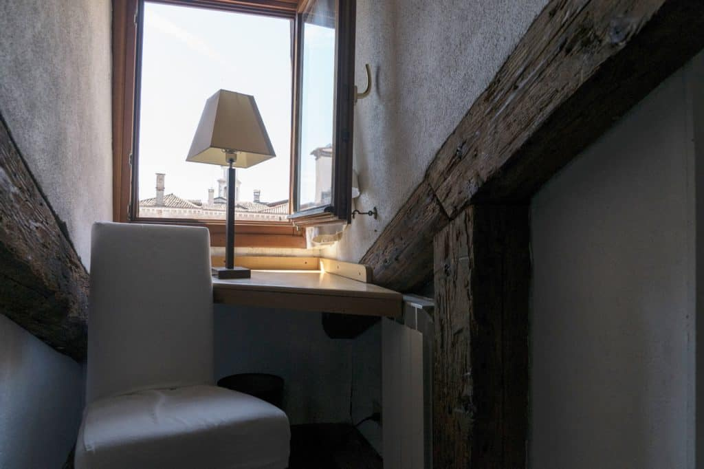 Small studio with chair and wooden beams - Altana Studio Apartment