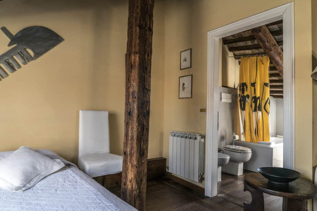 Right side of double bed with bathroom entrance - Altana Studio Apartment