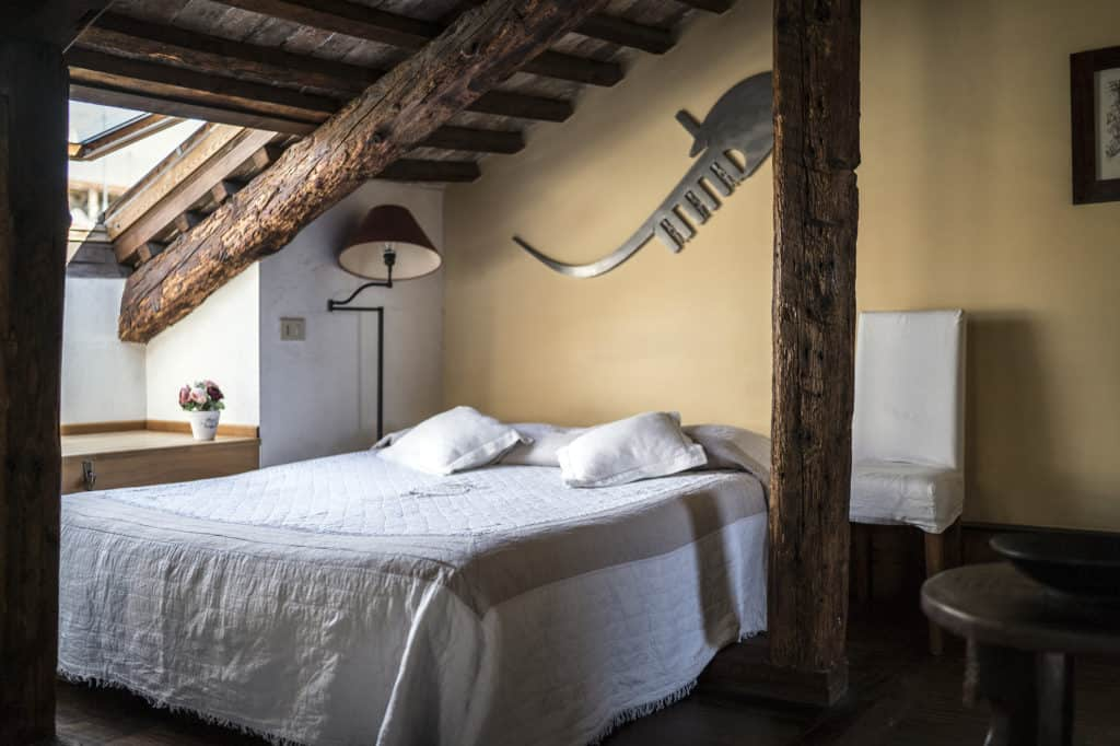 Left side of comfortable double bedroom with wooden beams and skylight window - Altana Studio Apartment