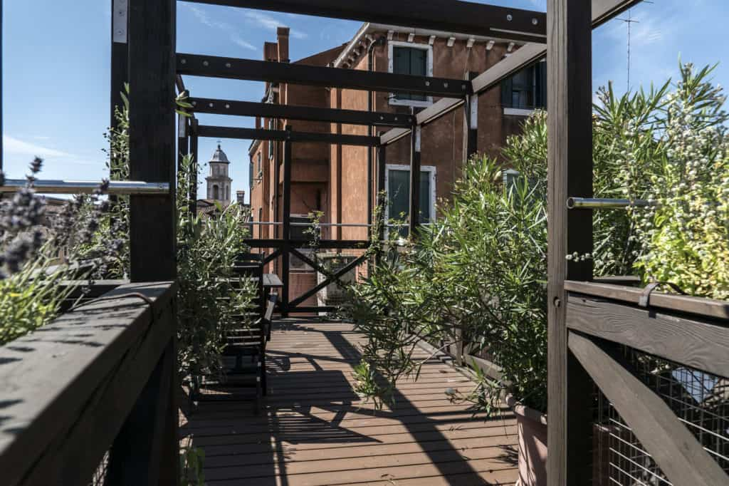 Right side of the open air wooden terrace with view of Venetian roofs - Altana Studio Apartment