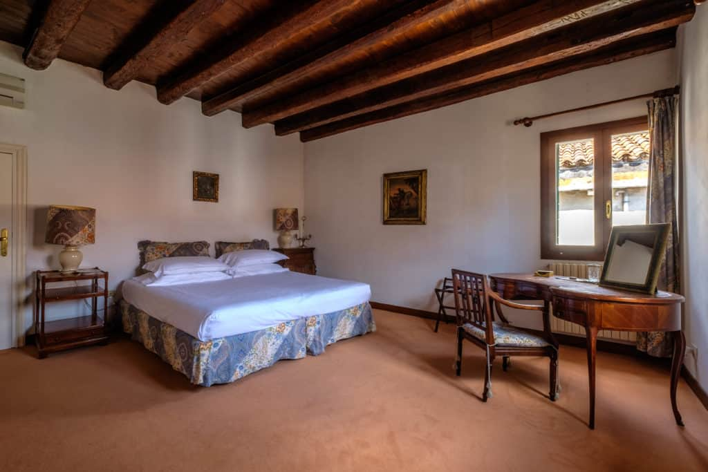 Large double bedroom with small antique desk and exposed beams - Ca' Affresco 1 Apartment