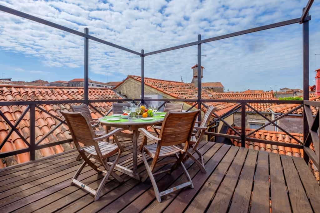 Wooden terrace with small dining table and view on the Venetian roofs - Ca' Affresco 1 Apartment
