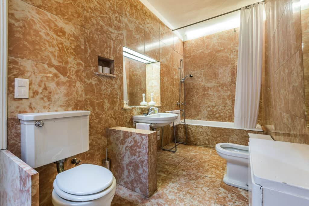 Large bathroom with marbled walls and floor and bathtub - Ca' Affresco 2 Apartment