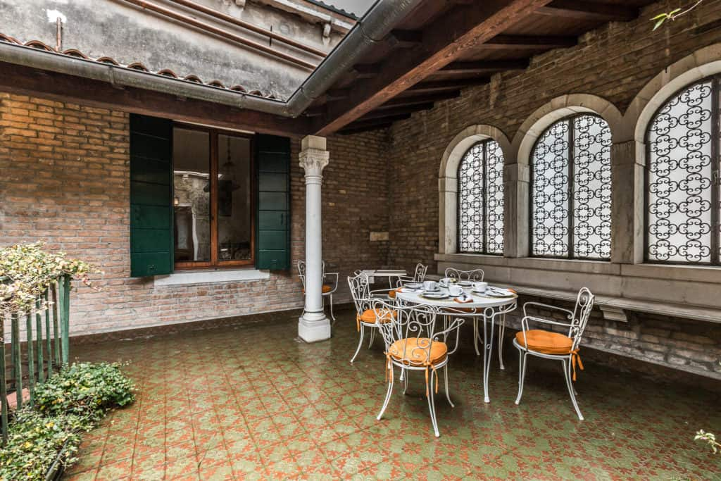 Left view of the semi-covered terrace with antique windows and columns - Ca' Affresco 2 Apartment