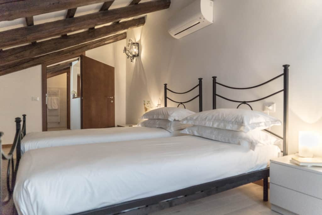 Left view of the large bedroom with exposed beams - Ca' del Capitano Apartment