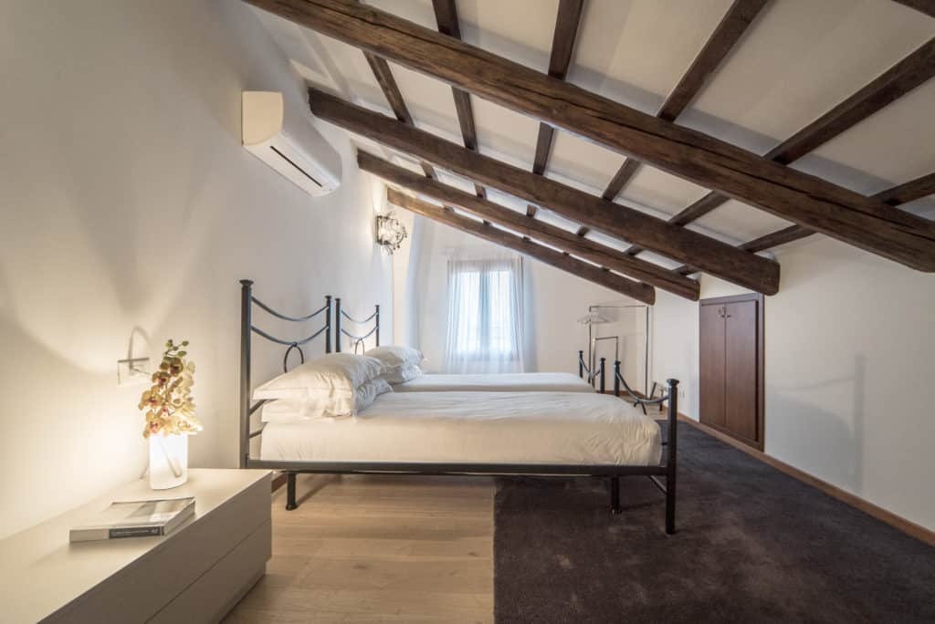 Right view of the large bedroom with exposed beams - Ca' del Capitano Apartment