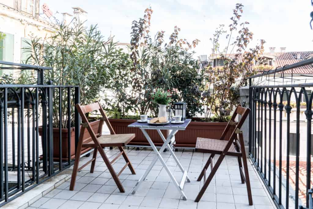 Luminous terrace with small dining table and view on the Venetian roofs - Ca' dell'Architetto Apartment
