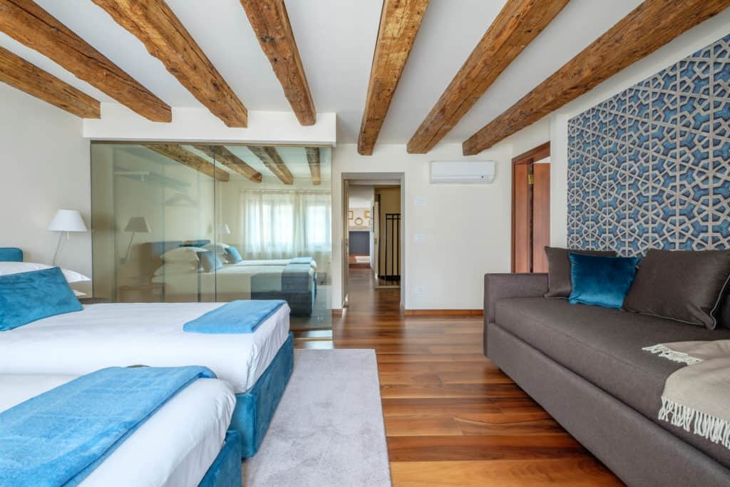 Right side of the double bedroom with sofa and exposed beams - Ca' Garzoni Moro - Lido Apartment