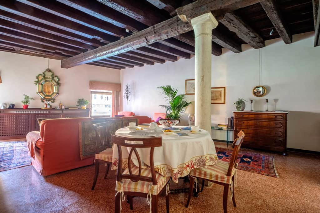 RIght view of the large and luminous living room with dining table, colums and exposed beams - Ca' Mocenigo Apartment