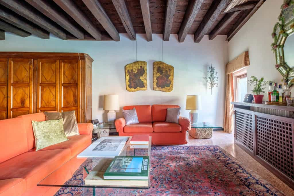 Left view of the large and luminous living room with vintage furnishing, colums and exposed beams - Ca' Mocenigo Apartment