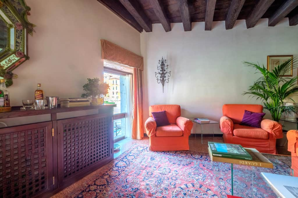 Living room with armchairs, large window, vintage furnishing and exposed beams - Ca' Mocenigo Apartment