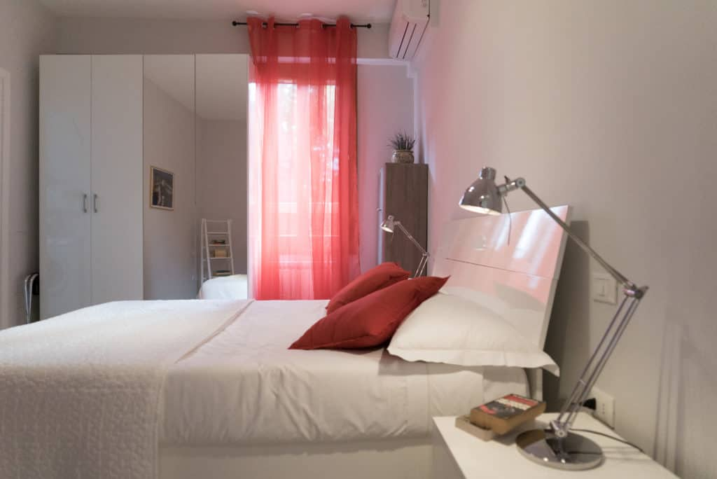 Left side of the bedroom with red curtains  and modern furnishing - Venier Apartment