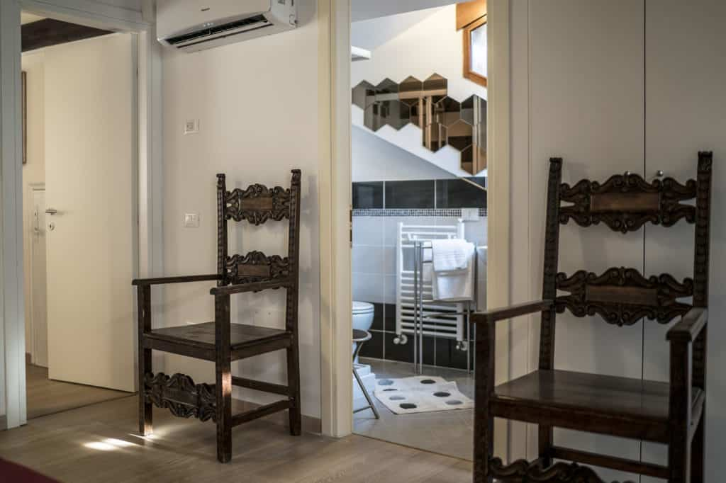 Hallway with antique chairs and entrance of the bathroom - Ca' Alba Apartment