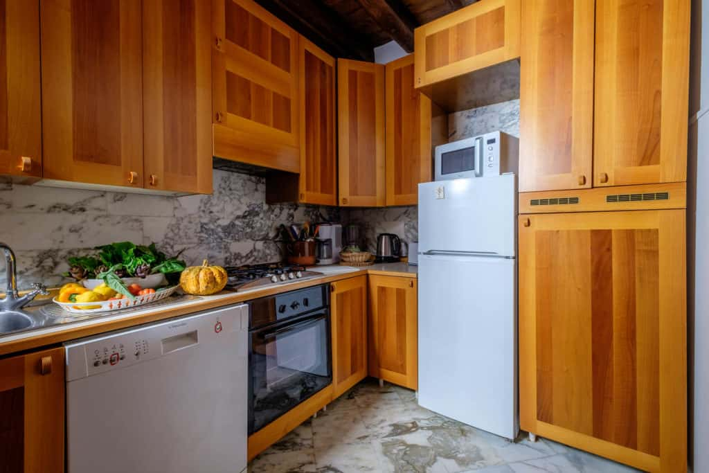 Luminous kitchen with wooden cabinets - Casa dell'Albero Apartment