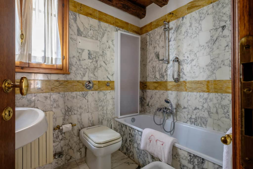 Right view of the small bathroom with bathtub, marbled walls and floor - Casa dell'Albero Apartment