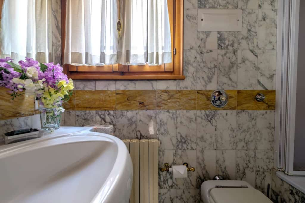 Detail of the small bathroom with marbled walls and floor - Casa dell'Albero Apartment