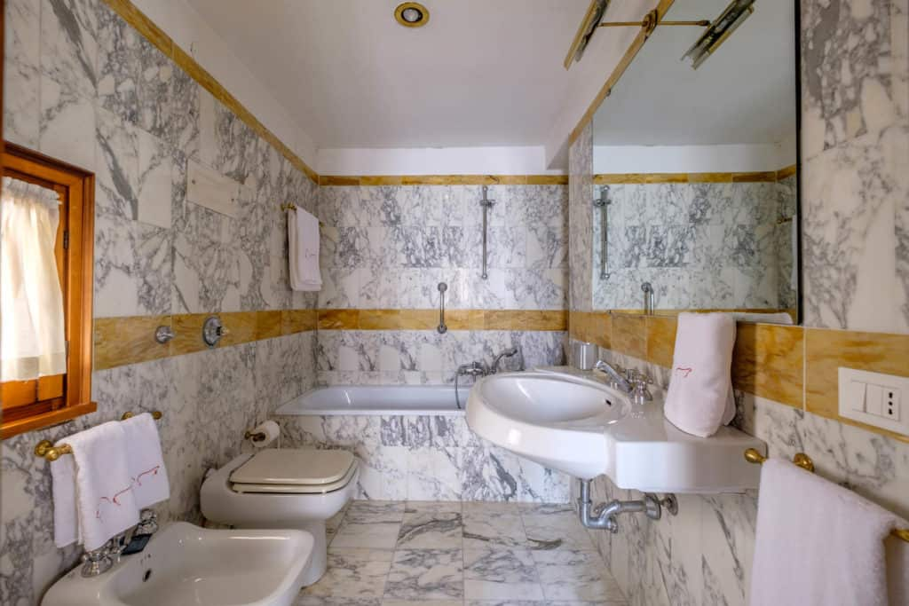 Large bathroom with bathtub, marbled walls and floor- Casa dell'Albero Apartment