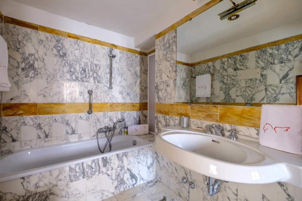 Bathroom with marbled bathtub and walls - Casa dell'Albero Apartment