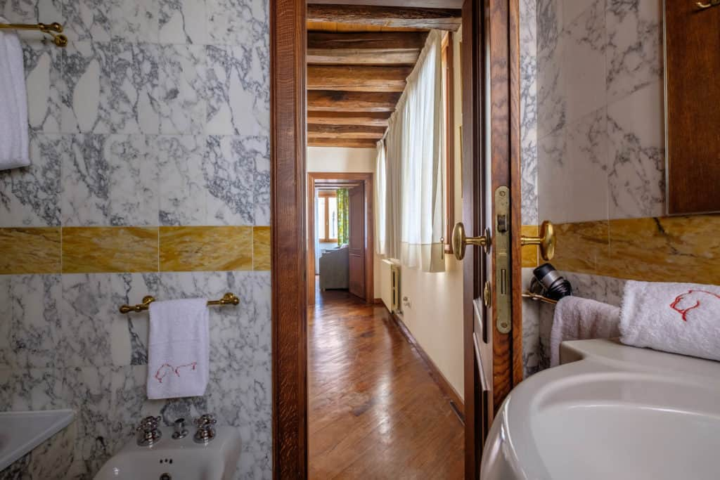 Entrance of the small bathroom with marbled walls and floor - Casa dell'Albero Apartment