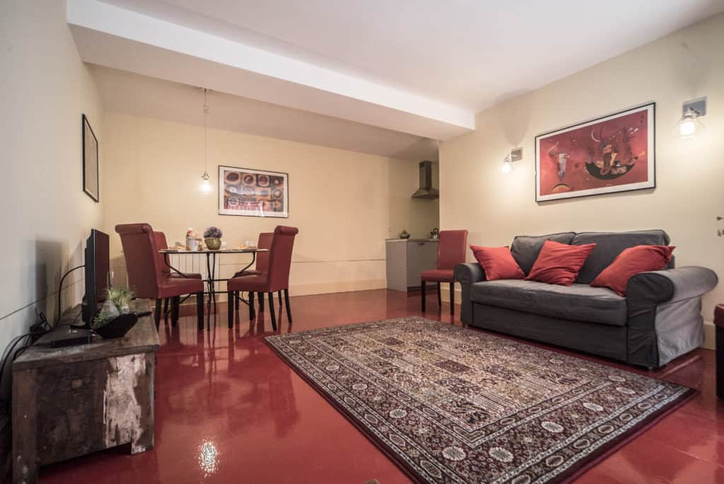 Entrance of the large living room with red floor and small dining table - Kandinskij House Apartment