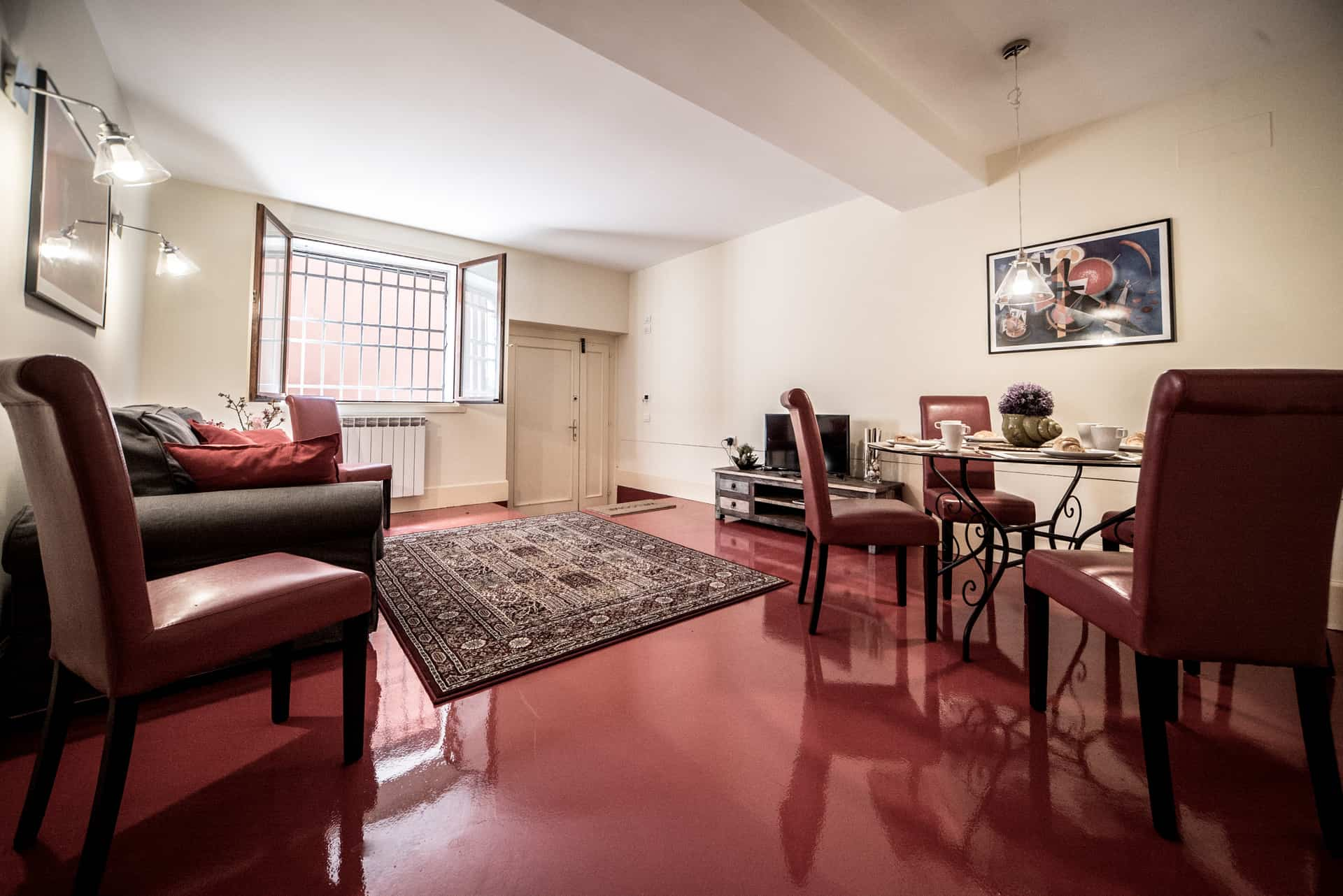 Large living room with red floor and small dining table - Kandinskij House Apartment