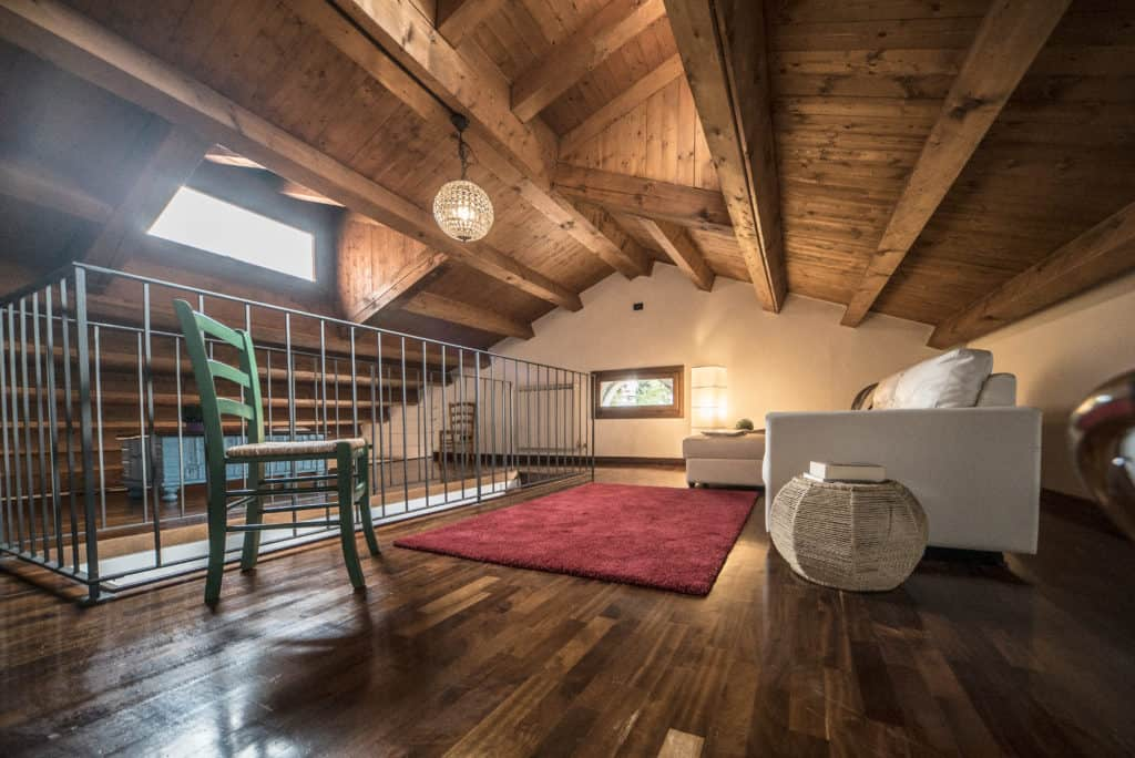 Large attic with living room and exposed beams - Mansarda Magritte Apartment