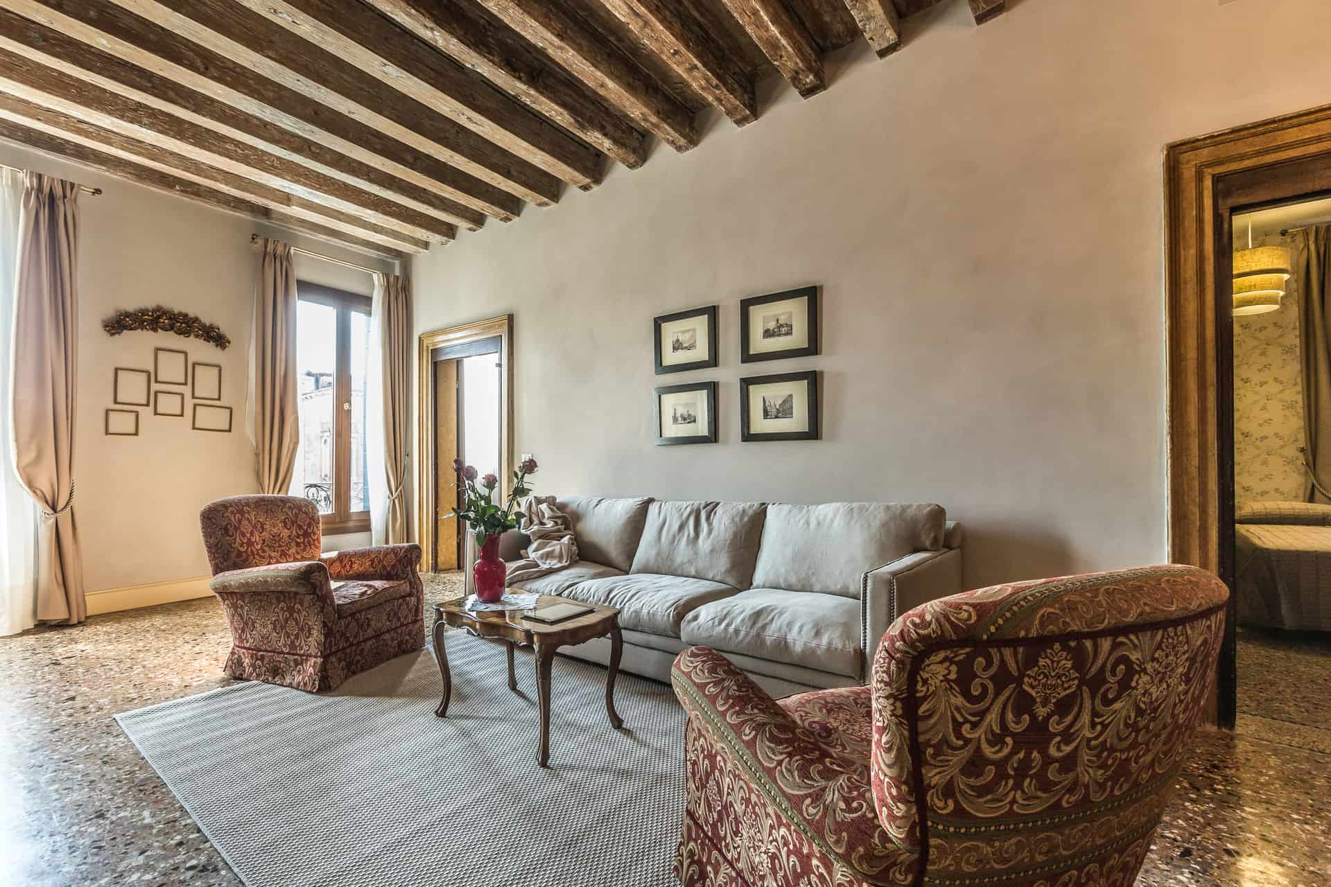 Left view of the luminous living room with vintage armchairs and large sofa - Palazzina Canal Apartment