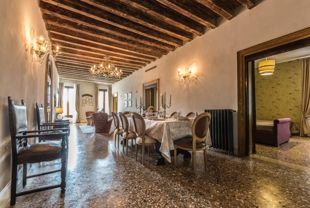 Large room with long dinner table with antique Venetian furnishing - Palazzina Canal Apartment