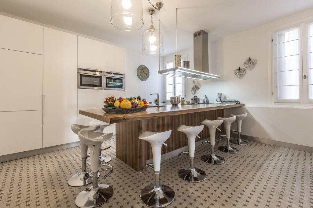 Left view of large modern kitchen with bar stools  - Palazzina Canal Apartment