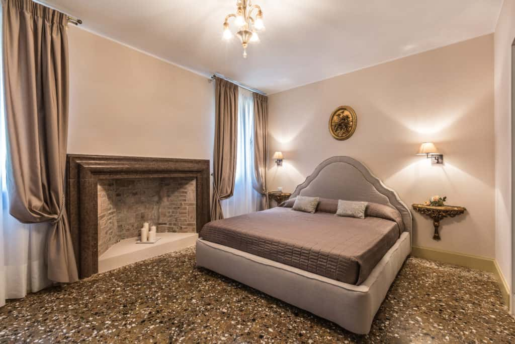 Large master bedroom with vintage furnishing and fireplace - Palazzina Canal Apartment