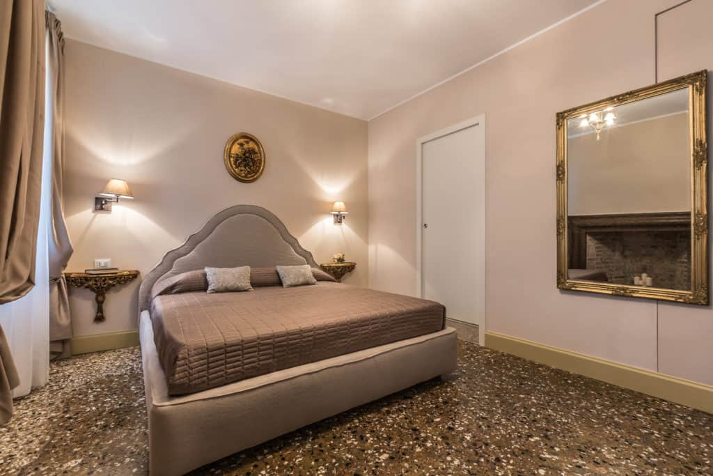 Right view of the large master bedroom with vintage furnishing and fireplace - Palazzina Canal Apartment