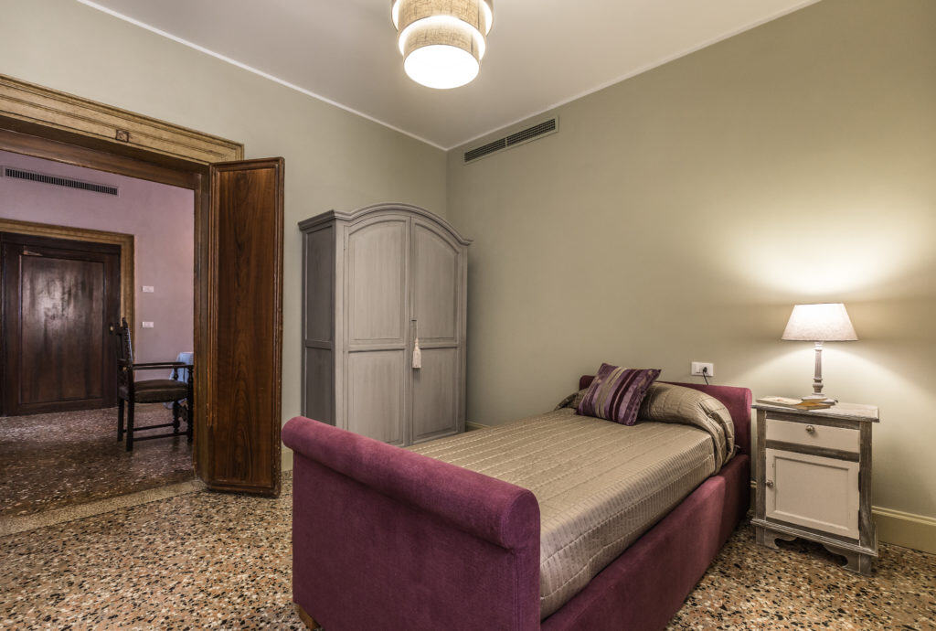 Large single bedroom with purple bed - Palazzina Canal Apartment