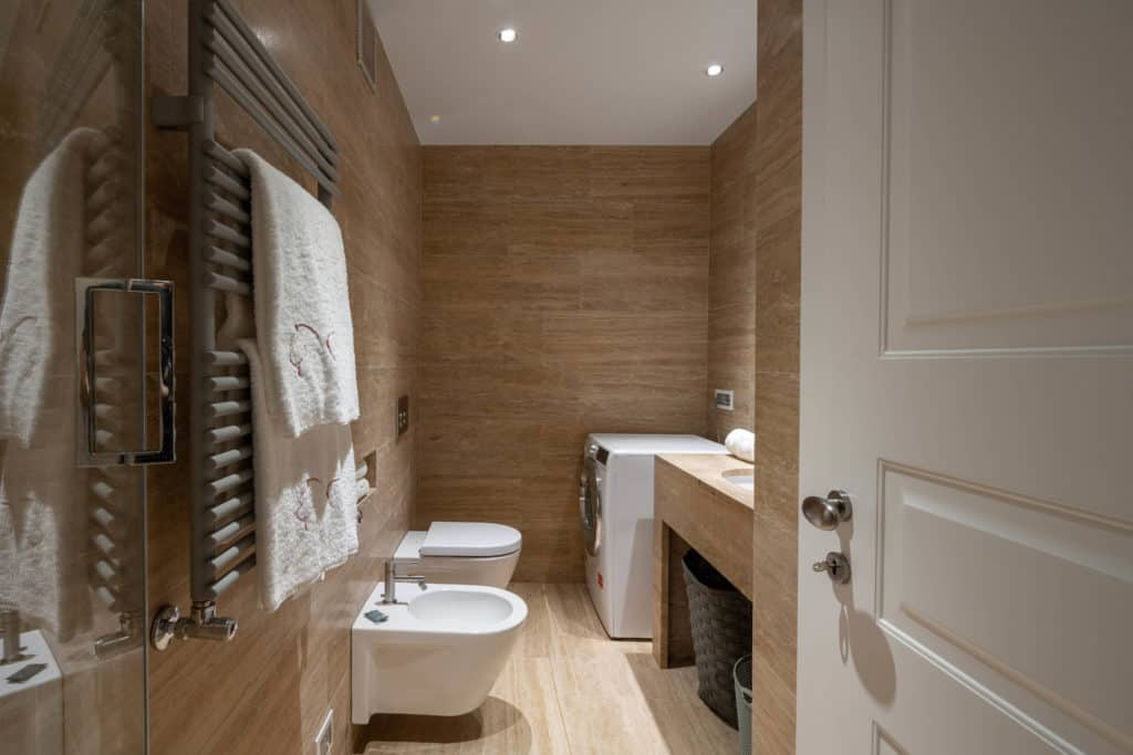 Left view of the contemporary small bathroom with washing machine - Palazzo Molin Massari Apartment