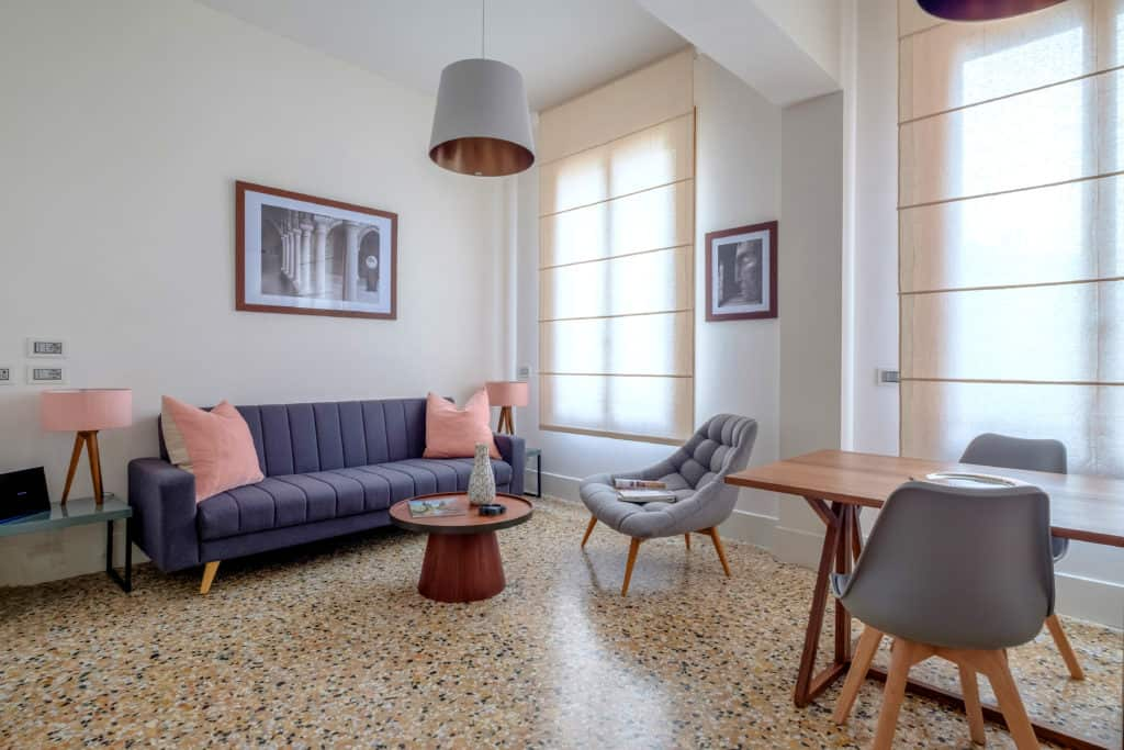 Left side of the luminous living room with large sofa and dining table - Palazzo Molin Tiziano Apartment