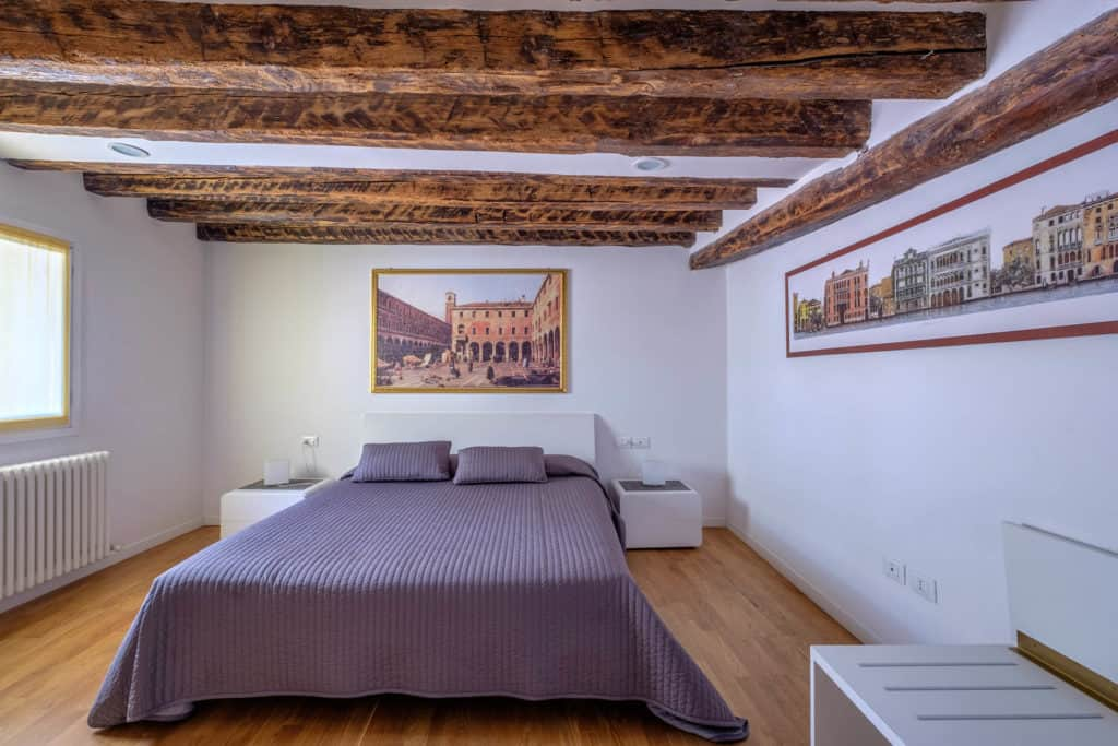 Large master bedroom with exposed beams - The Lion's 5 Apartment