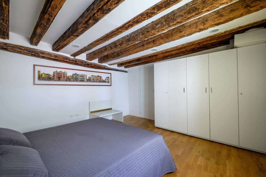Entrance view of the large master bedroom with exposed beams and wardrobe - The Lion's 5 Apartment