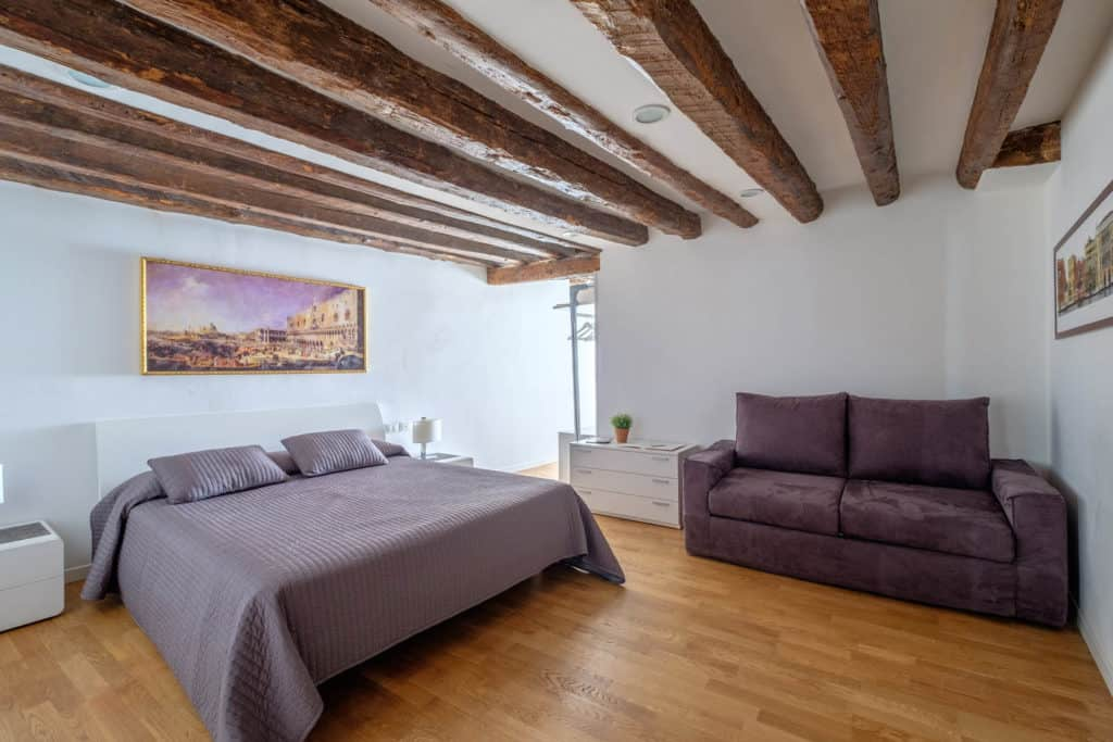 Right view of the luminous master bedroom with exposed beams and sofa - The Lion's 5 Apartment