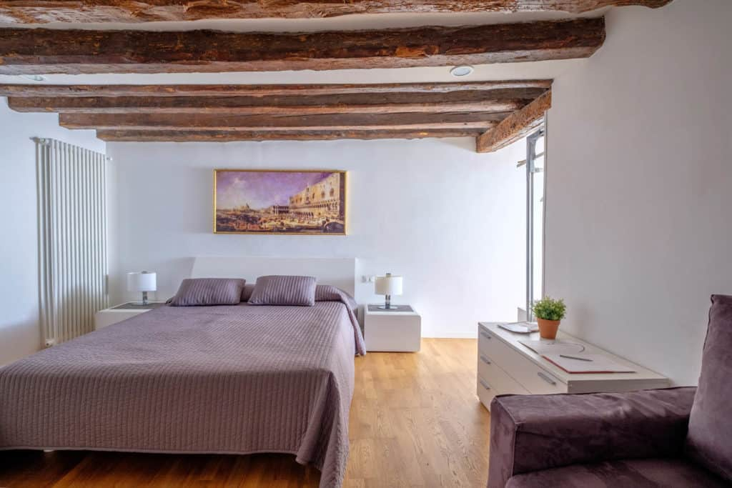 Luminous master bedroom with exposed beams and sofa - The Lion's 5 Apartment