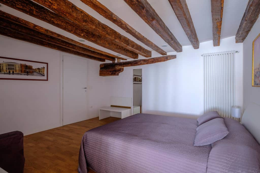 Left view of the luminous master bedroom with exposed beams and sofa - The Lion's 5 Apartment