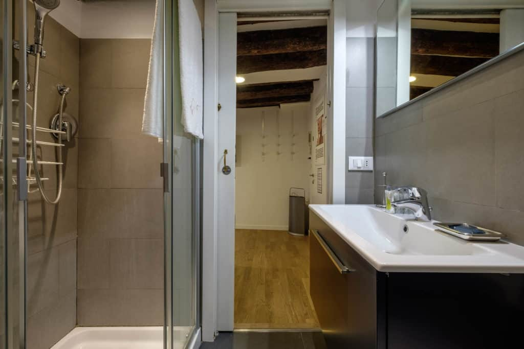 Left view of the small bathroom with modern furnishing - The Lion's 5 Apartment