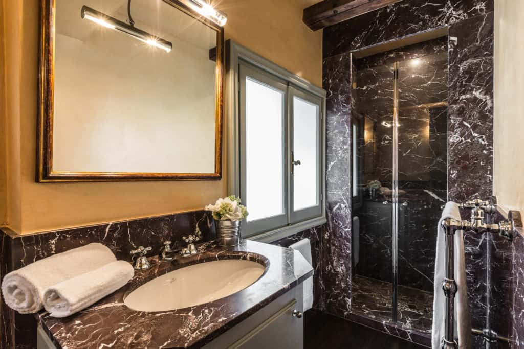 Left view of the large bathroom with marbled sink and shower - The Venetian Penthouse Apartment