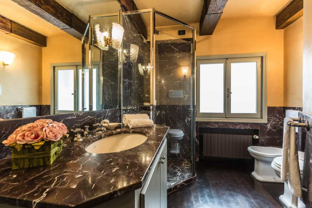 Large bathroom with marbled sink and shower - The Venetian Penthouse Apartment