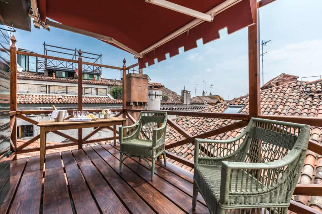 Small wooden terrace with armchairs and view on the Venetian roofs - The Venetian Penthouse Apartment