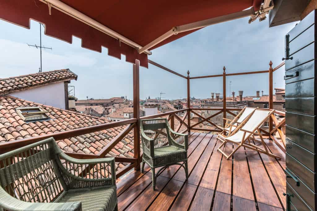 Right view of the small wooden terrace with armchairs and view on the Venetian roofs - The Venetian Penthouse Apartment
