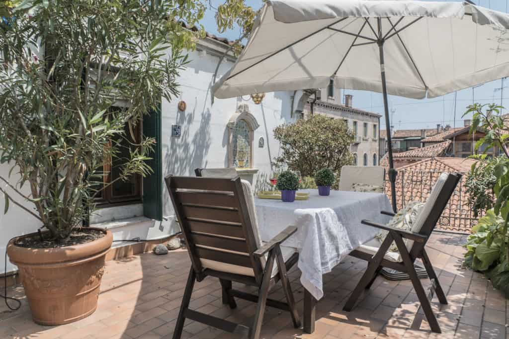 Large terrace with dining table and view on the Venetian roofs - Three Terraces Apartment