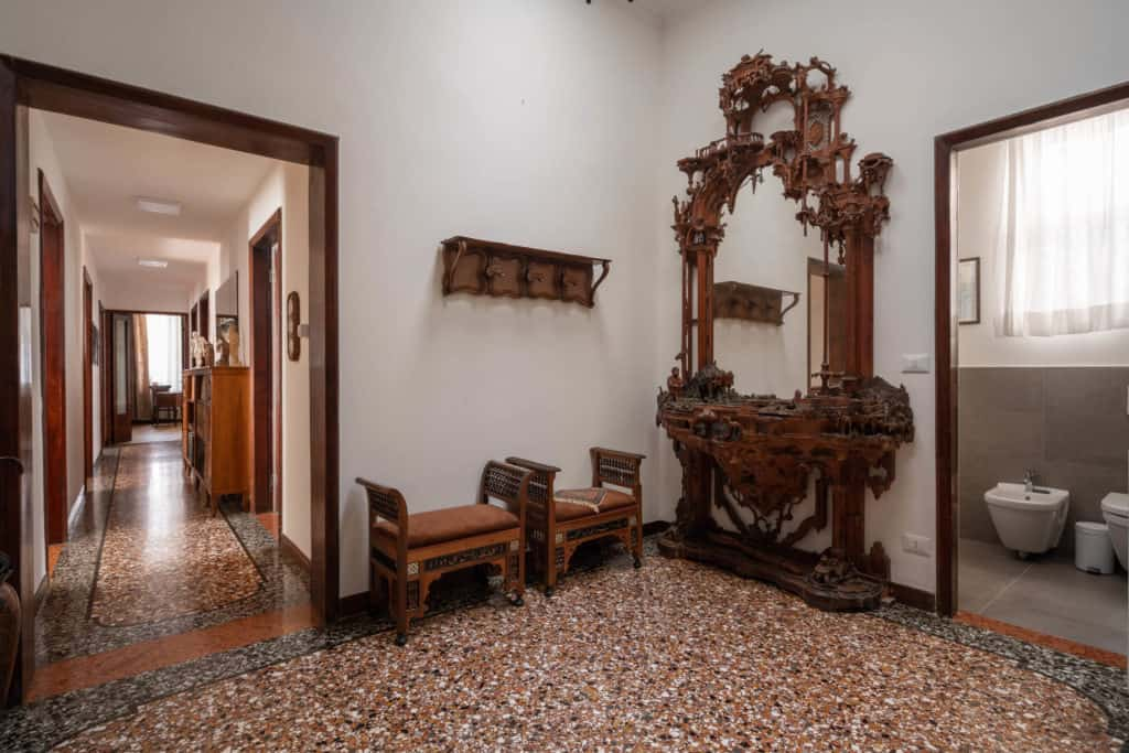 Hallway with antique furnishing and entrance door of the bathroom - Accademia 2 Apartment